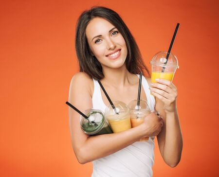 Young attractive brunette woman holding takeaway cup of smoothie. Happy girl posing on red background. Healthy eating concept. Imagens