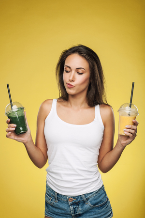 Young attractive brunette woman holding takeaway cups of smoothie. Happy girl posing on yellow background. Healthy eating concept.