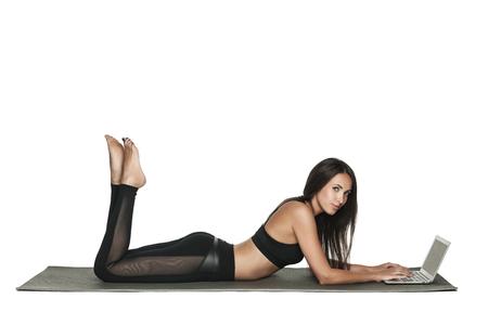 Junge Frau arbeitet an ihrem Laptop beim Liegen auf einer Matte in Yoga-Klasse. Besetzte Frau verbindet Arbeit und Fitness. Isoliert auf weiß.
