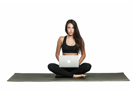 Young woman working on her laptop while sitting on a mat in yoga class. Busy woman combines work and fitness. Isolated on white.