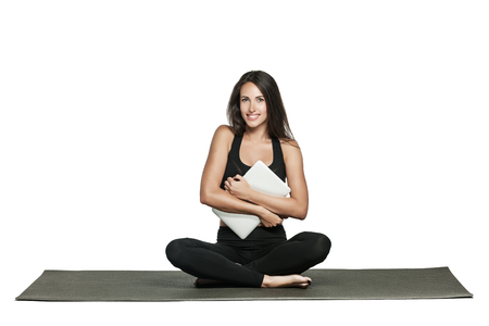 Young woman holds her laptop while sitting on a mat in yoga class. Busy woman combines work and fitness. Isolated on white.