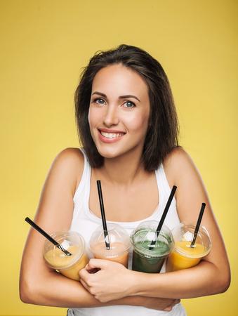 スムージーのテイクアウト カップを保持している若い魅力的なブルネット女性。黄色の背景にポーズをとって幸せな女の子。健康的な食事のコンセ
