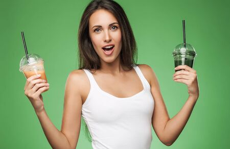 スムージーのテイクアウト カップを保持している若い魅力的なブルネット女性。緑の背景にポーズをとって幸せな女の子。健康的な食事のコンセプ