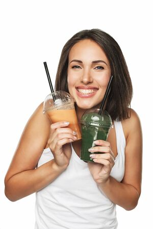 Young attractive brunette woman holding takeaway cups with smoothie. Healthy eating concept. Isolated on white. Standard-Bild