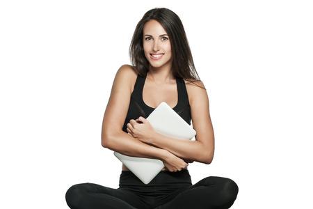 若い女性は、ヨガのクラスでマットに座って彼女のラップトップを保持します。忙しい女性は、仕事とフィットネスを組み合わせたものです。白で