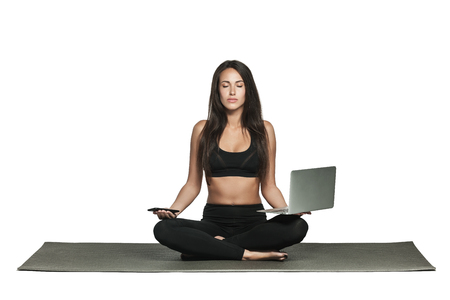 Young woman holds her laptop and smartphone in hands while sitting on a mat in yoga class. Busy woman combines work and fitness. Isolated on white.