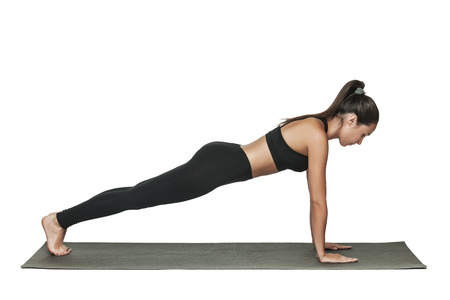 Woman doing plank. Young attractive brunette with fit body working out in yoga class. Healthy lifestyle concept. Isolated on white. Imagens - 85166928