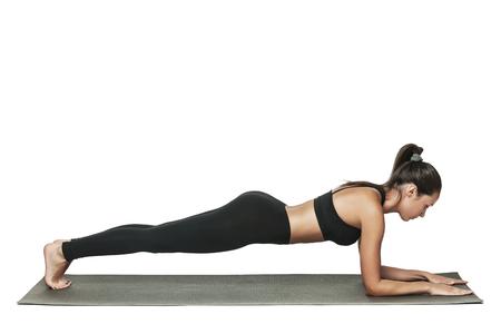 Vrouw doet plank. Jonge aantrekkelijke brunette met fit lichaam trainen in yogales. Gezond levensstijlconcept. Geïsoleerd op wit.