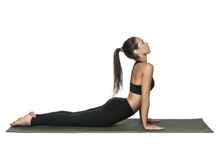 若者は、ヨガのクラスで女性を合わせてください。ヨガの練習のポニーの尾を持つ魅力的なブルネットの女性。健康的なライフ スタイルとスポーツ