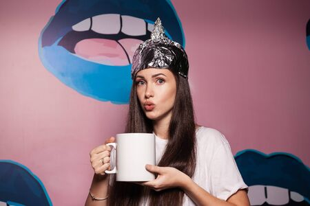Attractive young woman wearing tinfoil hat for protection. Conspiracy theory concept. Woman holding a cup of coffee Standard-Bild