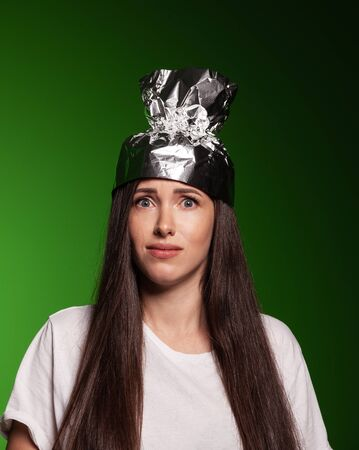 Attractive young woman wearing tinfoil hat for protection. Conspiracy theory concept.