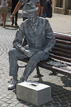 Lviv, Ukraine - September 11, 2011: Living statue - a man playing chess on the bench in the centre of Lviv, Ukraine.