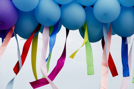 Blue balloons with developing colorful ribbons  photo