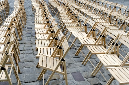 sameness: Empty wooden chairs on the pavement