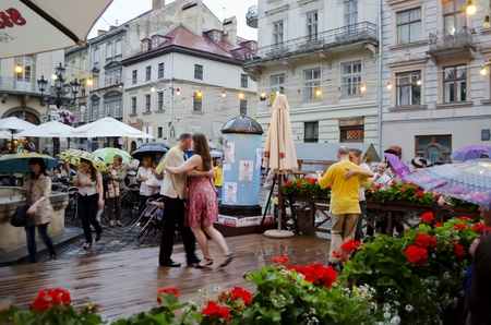 lemberg: LVIV, UKRAINE - JUNE 13: In the center of Lviv opened dance floor to all comers on June 13, 2012 in Lviv, Ukraine. In the picture are dancing in the rain unknown guests EURO 2012. Editorial