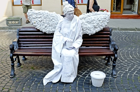 LVIV, UKRAINE - AUGUST 04, 2012: Entertainment for the tourist in centre of Lviv: Living statue - a woman in the image of a white angel.