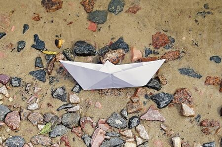 Paper boat lying on the shore after the crash