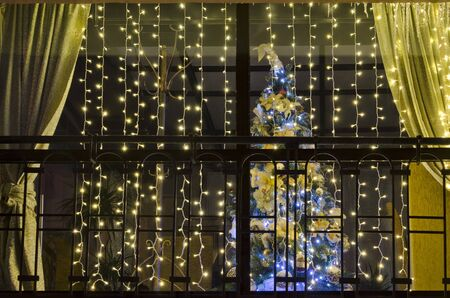 Beautiful Christmas tree outside the window, decorated with golden curtains and garlands Zdjęcie Seryjne