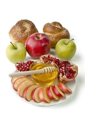 Stilleven - challah, appels, granaatappel en kom honing over wit. Illustratie van Rosj Hasjana (Joods Nieuwjaar) of Verlosser van de Apple feestdag Stockfoto