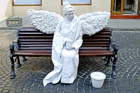 LVIV, UKRAINE - AUGUST 04: Entertainment for the tourist in Lvov: Living statue - a white angel sitting on a bench on August 04, 2012 in Lvov, Ukraine