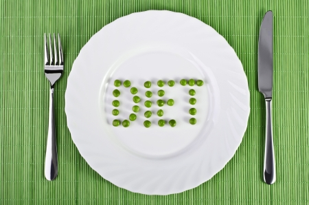 Tableware - the word diet of green peas on a white plate with a fork and knife on the sides