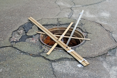 Dangerous manhole without a cover laid wooden planks close-up Stock Photo