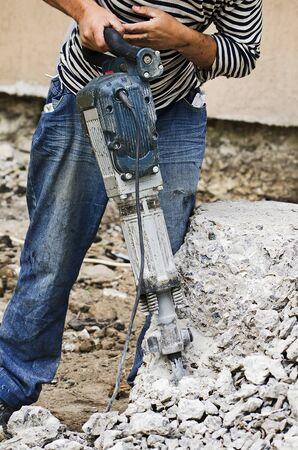 Builder breaks concrete blocks using a jackhammer Stock Photo
