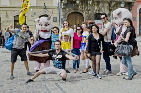 worl: LVOV, UKRAINE - APRIL 27: Tourists are photographed with fairy tale characters in the heart of the city on the day of celebration of the city on April 27, 2013 in Lviv, Ukraine Editorial