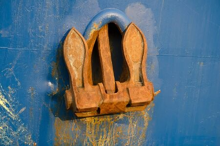 ship anchor: Rusty anchor marine ship close-up against the blue of the ship