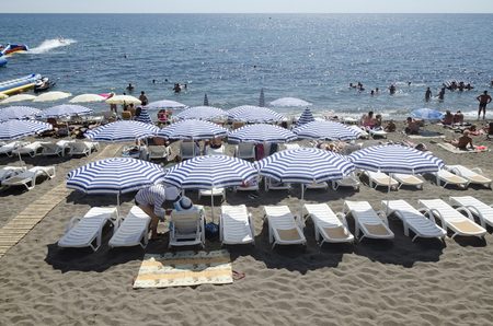 sudak: SUDAK, CRIMEA, RUSSIA - AUGUST 24: Resting under a sun umbrella on the beach on august 24, 2014 in Sudak, Crimea, Russia Editorial