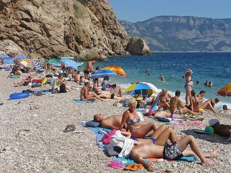 vacationers: SEVASTOPOL, CRIMEA, RUSSIA - AUGUST 20: Vacationers people on beach Vasili in Balaclava on august 20, 2014 in, Sevastopol, Crimea, Russia Editorial