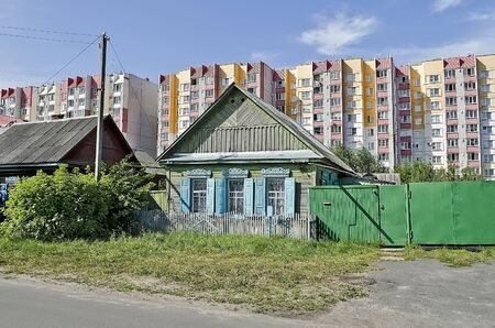 merger: Merger of the village and town - Cottage on the background of high-rise buildings. Gomel, Belarus
