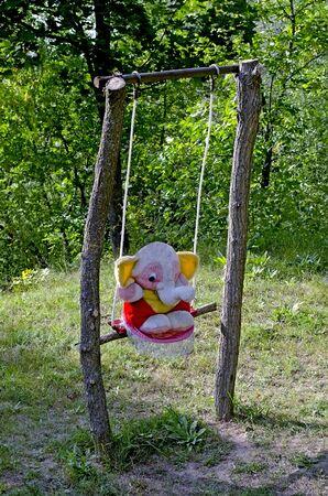 toy elephant: Toy elephant on teeter close-up against trees Stock Photo
