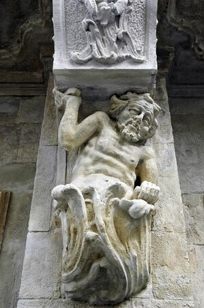 lvov: Old sculpture of a man holding up a balcony on the building in Lvov, Ukraine Stock Photo