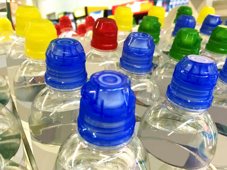 Plastic bottles of mineral water with colored caps in the supermarket