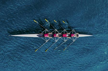 Équipe d'aviron des femmes sur l'eau bleue, vue de dessus Banque d'images