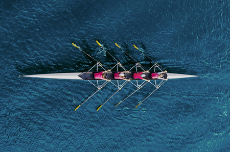 Women's rowing team on blue water, top view