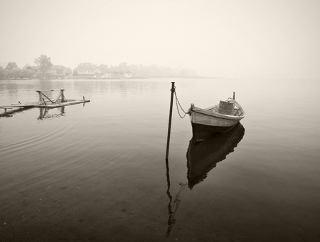 boat dock: Old wooden boat in fog, black and white Stock Photo