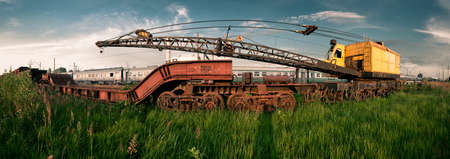Old colored and rusted railway crane on rails