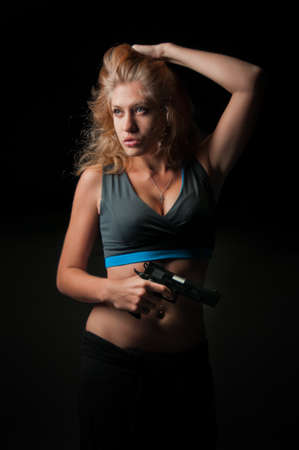 Beauty woman with pistol portrait on black background