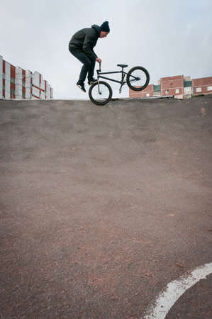 Biker doing footjam tailwhip trick with houses on background Stock Photo