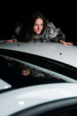 Pretty girl in fur coat laying on car hood