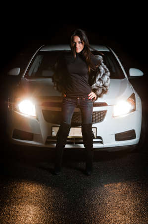 enabled: Pretty girl in front of car with enabled headlights Stock Photo