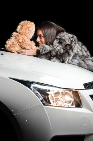 Girl laying on white car hood with plush teddy bear
