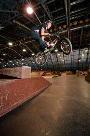 Biker doing bar spin drop trick in wooden park