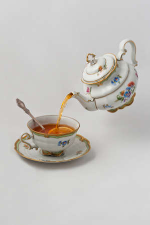 teacup: Tea pours into a cup with lemon from teapot