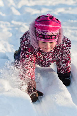 Baby crawls all fours on snow and smile