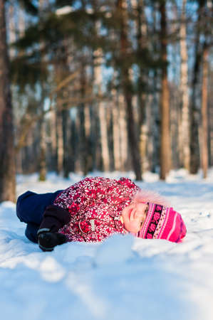 Baby lays on snow in wood, looks and smile Stock Photo