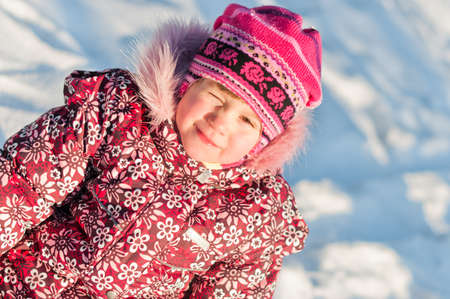 frowns: Baby sits on snow, frowns and smile, portrait