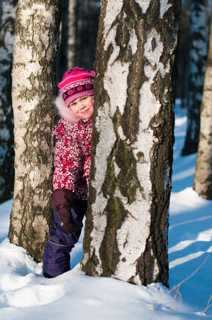 Baby stands behind a tree in wood, hiding Stock Photo